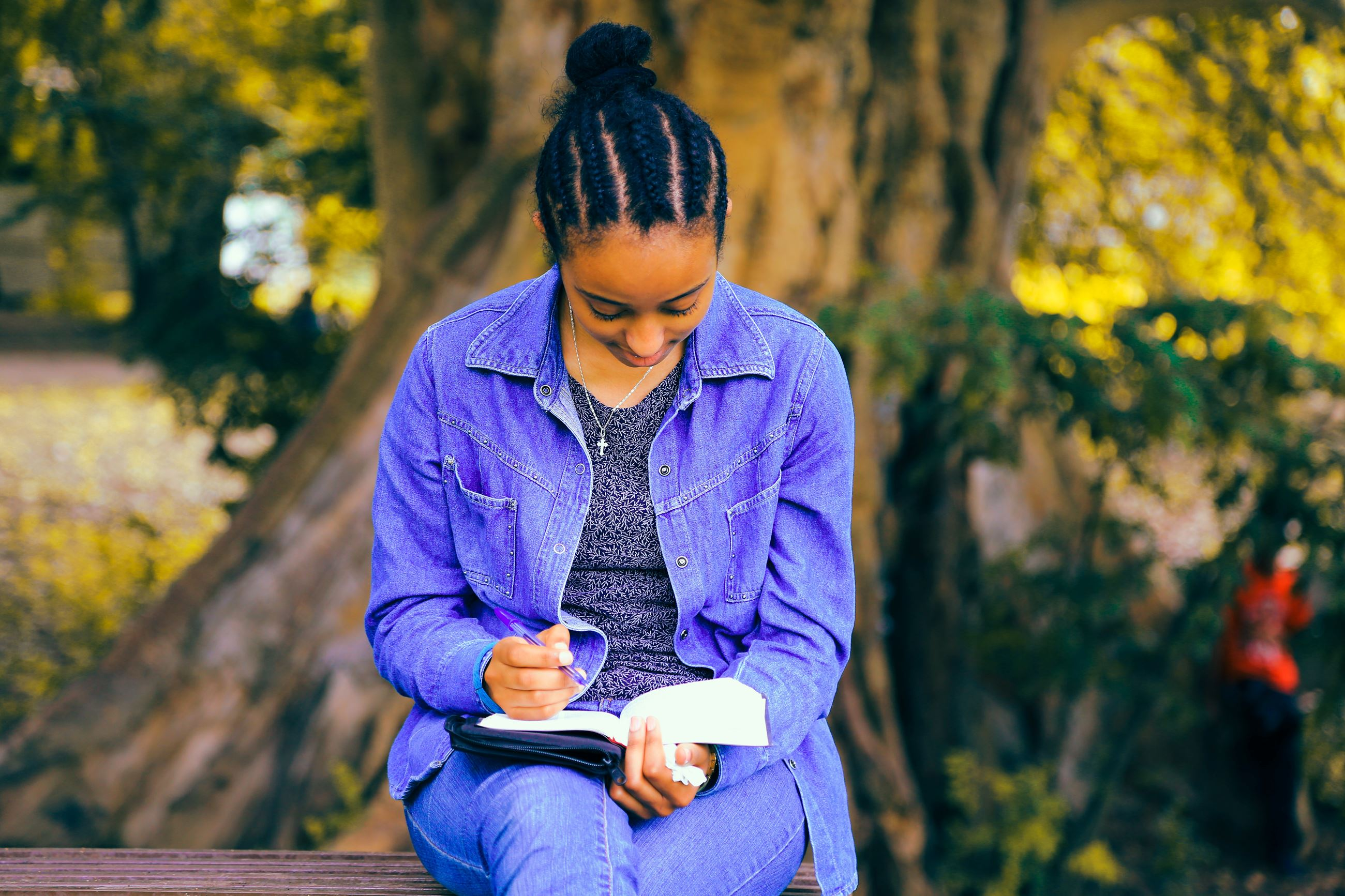Photo by Gift Habeshaw on Unsplash. A girl writing in a journal on a park bench under a tree.