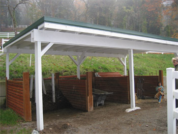 A covered shed with compost piles