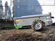 A grey manure spreader on wheels